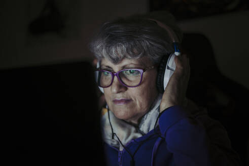 Close-up of senior teacher wearing headphones while using laptop at home - OIPF00069