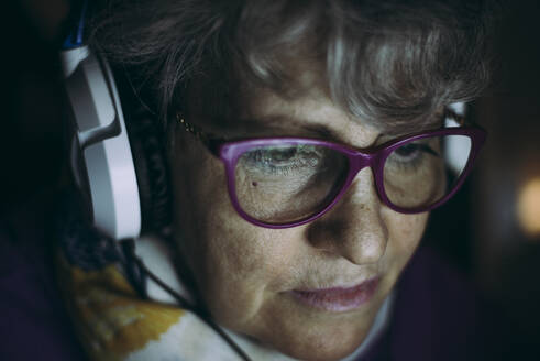 Close-up of senior teacher wearing headphones while working at home - OIPF00072