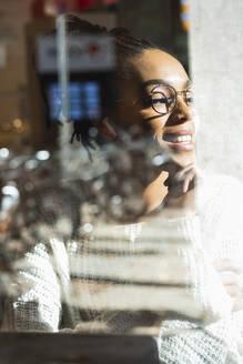 Smiling young woman wearing eyeglasses looking through window at cafe - PNAF00408
