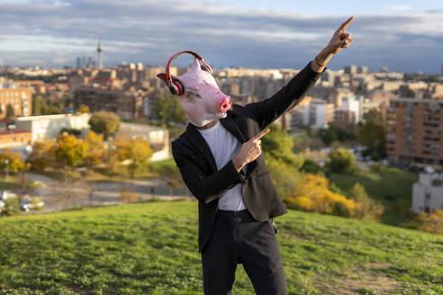 Male entrepreneur wearing pig mask and wireless headphones posing on hill against city - GGGF00589