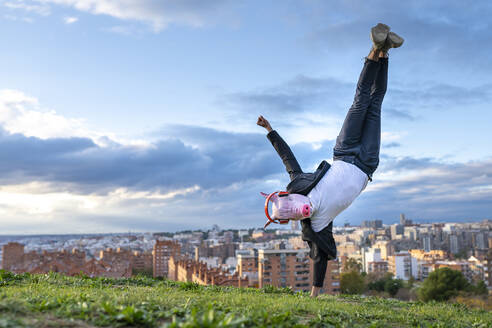 Businessman wearing pig mask doing handstand on hill in city against sky - GGGF00601