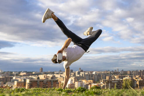 Flexible young man wearing virtual reality headset while doing handstand on hill in city against sky - GGGF00616