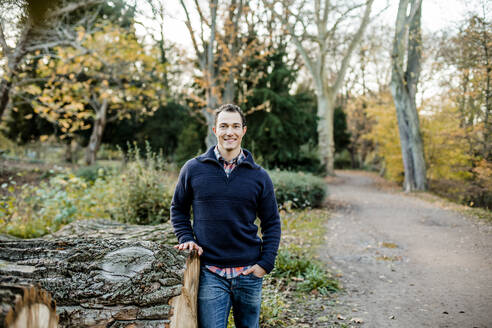 Smiling handsome man with hand in pocket standing in front of trees at public park - KVF00146