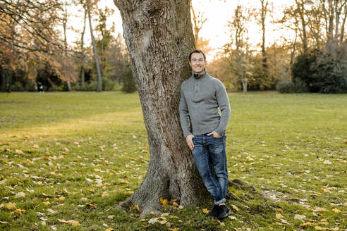 Smiling mid adult man standing by tree trunk in public park - KVF00149