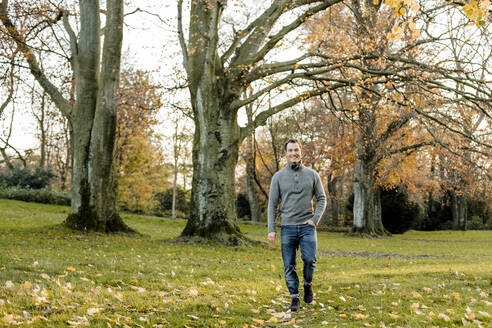 Smiling man walking on grass in front of trees in public park - KVF00152