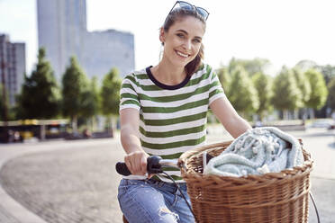 Smiling beautiful woman riding bicycle in city during weekend - ABIF01282
