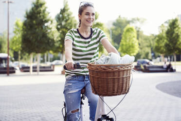 Happy beautiful woman riding bicycle on street in city during weekend - ABIF01288
