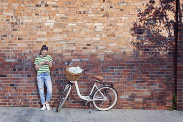 Smiling woman text messaging through smart phone while bicycle parked on footpath against brick wall - ABIF01291