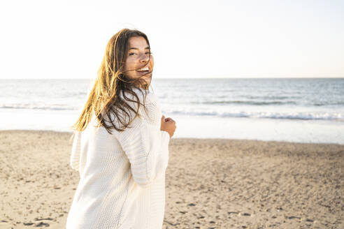 Cheerful beautiful woman spending leisure time at beach during sunny day - UUF22345