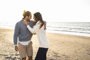 Happy young couple embracing at beach during sunny day - UUF22354