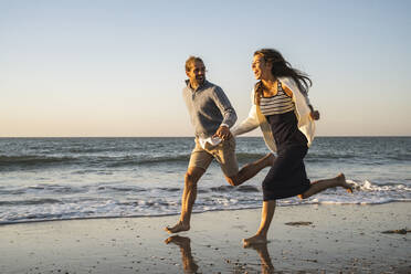 Cheerful young couple holding hands while running at beach during sunset - UUF22357