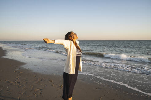 Carefree young woman standing at beach with arms outstretched during sunset - UUF22363