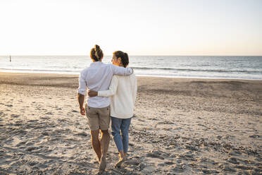 Young couple with arms around walking at beach during sunset - UUF22369