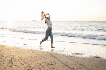 Carefree young woman holding jacket while running at beach against clear sky during sunset - UUF22378