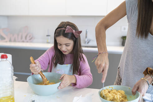 Daughter preparing muffin standing by mother in kitchen - SNF00890