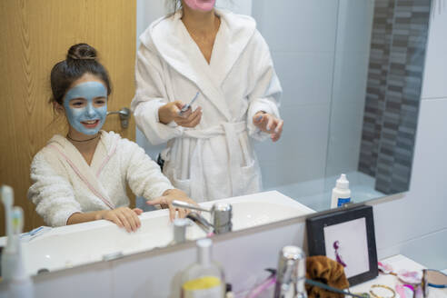 Reflection of daughter with facial mask standing by mother in bathroom - SNF00941