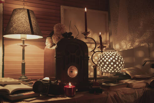Burning candles and illuminated old fashioned lamp placed on table with vintage clock in cozy room with dim light - ADSF19638