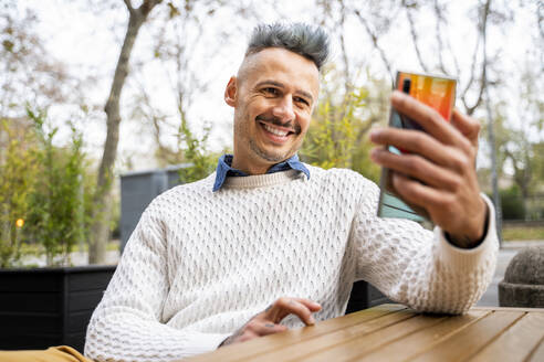 Smiling man taking selfie on smart phone while sitting in outdoor cafe - AFVF07934