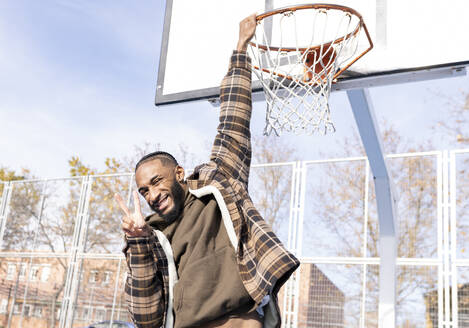 Happy young man gesturing peace while hanging on basketball hoop in court during sunny day - JCCMF00323