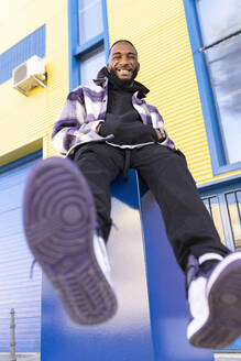 Happy male rapper with hands in pockets showing sole of shoe against built structure - JCCMF00353