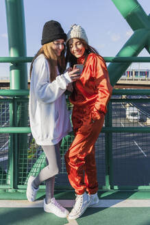 Smiling female friends using mobile phone while standing on bridge - JRVF00025