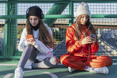 Female friends wearing knit hat and and headphones using mobile phones while sitting on bridge - JRVF00028