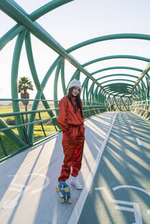 Young woman with skateboard standing on bridge - JRVF00049