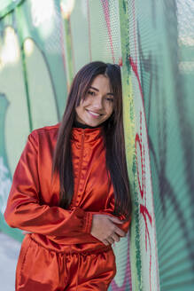 Woman smiling while leaning on graffiti fence - JRVF00052