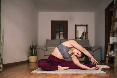Young woman with arms raised practicing yoga while sitting on mat at home - GRCF00593