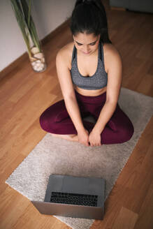 Young woman using laptop while sitting on exercise mat at home - GRCF00599