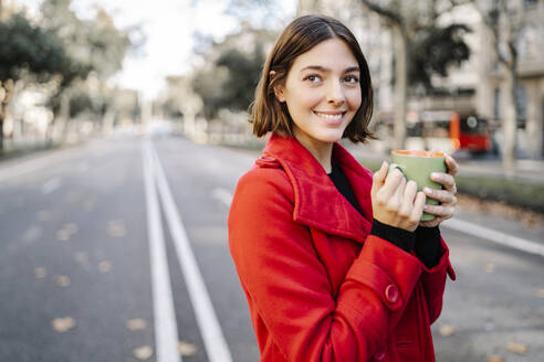 Happy young woman contemplating while holding coffee cup on road - JCZF00392