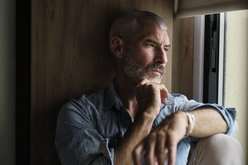 Handsome mature man contemplation while looking through window at home - AODF00144
