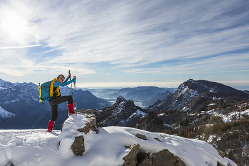 Male hiker climbing on top of mountain against sky, Orobic alps, Lecco, Italy - MCVF00693