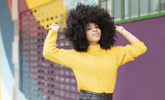 Curly hair woman smiling while standing against multi colored wall - JCCMF00377