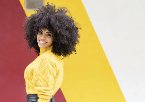 Curly hair woman smiling while standing against multi colored wall - JCCMF00386