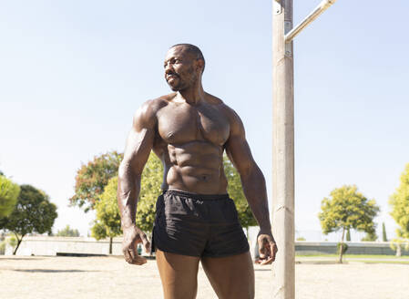 Shirtless male athlete looking away in park on sunny day - JCCMF00430
