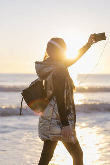 Mid adult woman taking selfie with smart phone against sea during sunset - JRVF00086
