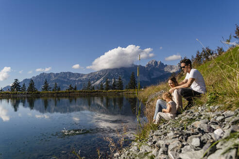 Family with little daughter sitting together on shore of alpine lake - DIGF13947