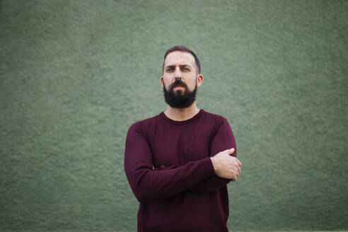 Bearded man with arms crossed standing against green wall - MIMFF00384