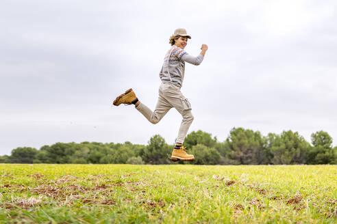 Young man jumping and posingmid-airin grassy field - GGGF00652