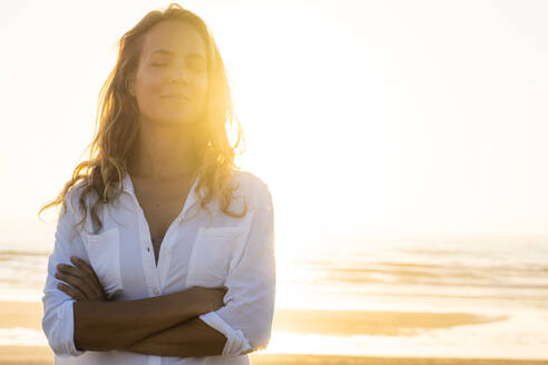 Woman standing with eyes crossed at beach during sunset - SBOF02327