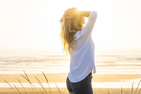 Woman with hands behind head standing at beach during sunset - SBOF02330