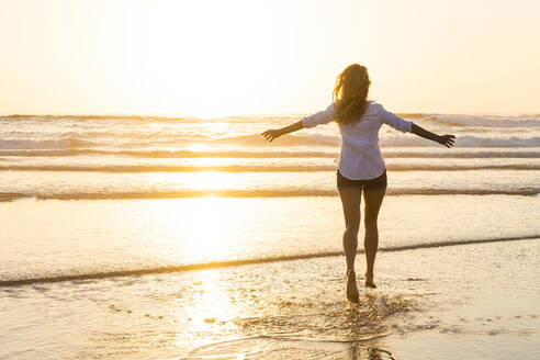 Carefree woman with arms outstretched running toward sea during sunset - SBOF02333