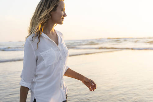 Smiling woman looking away while standing against sea during sunset - SBOF02342