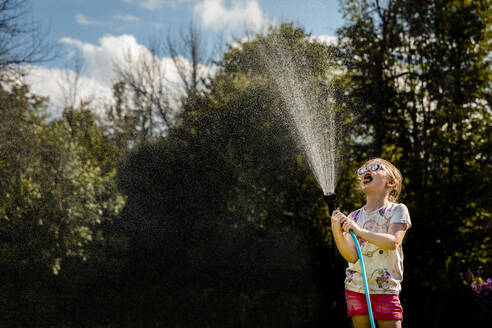 Playful girl with mouth open holding garden hose in yard - AWAF00016