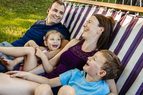 Family laughing while relaxing on hammock during weekend - AWAF00021