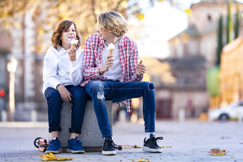 Smiling boy and man eating ice cream while sitting on bench - GGGF00661