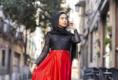 Portrait of young woman wearing black hijab standing outdoors - JCCMF00488