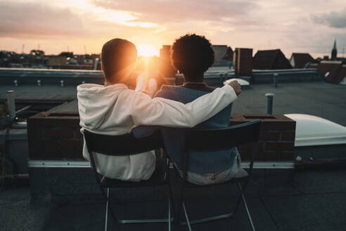 Rear view of man and woman sitting on building rooftop during sunset - MASF21109