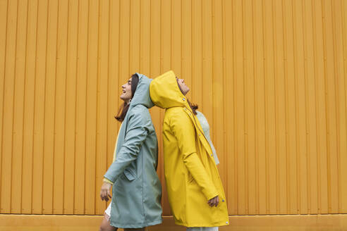 Young sister wearing blue and yellow raincoats standing back to back against wall - AXHF00012